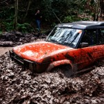 Orange Land Rover Discovery in muddy water